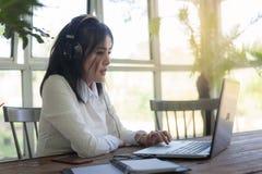 Молодая азиатская женщина работая с компьтер-книжкой в кофейне Стоковые Изображения
