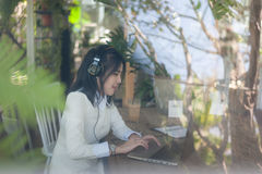 Молодая азиатская женщина работая с компьтер-книжкой в кофейне Стоковая Фотография RF