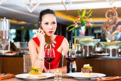 Молодая азиатская женщина сидя в ресторане Стоковые Фотографии RF