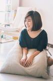 Молодая азиатская женщина сидя на поле в живущей комнате Стоковое Фото