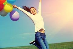 Молодая азиатская женщина скача с покрашенными воздушными шарами стоковые изображения