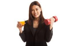 Молодая азиатская женщина с апельсиновым соком питья гантели Стоковая Фотография