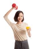 Молодая азиатская женщина с апельсиновым соком питья гантели Стоковые Изображения RF