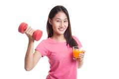 Молодая азиатская женщина с апельсиновым соком питья гантели Стоковые Изображения