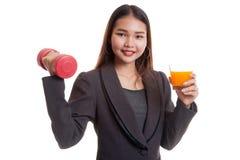 Молодая азиатская женщина с апельсиновым соком питья гантели Стоковое Фото