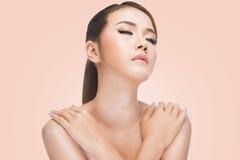 Молодая азиатская женщина с пересеченными оружиями очистите кожу отдыхая после skincare, на розовой предпосылке Стоковое фото RF