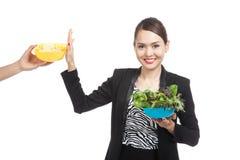 Молодая азиатская женщина с салатом говорит нет к картофельным стружкам Стоковые Фото