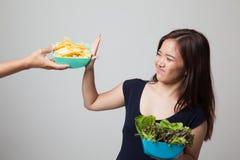 Молодая азиатская женщина с салатом говорит нет к картофельным стружкам Стоковая Фотография RF