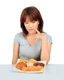 Молодая азиатская женщина с donuts на таблице Стоковые Изображения RF