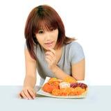 Молодая азиатская женщина с donuts на таблице Стоковые Фотографии RF