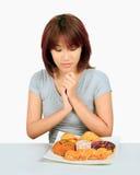 Молодая азиатская женщина с donuts на таблице Стоковая Фотография RF