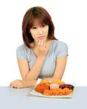Молодая азиатская женщина с donuts на таблице Стоковые Фото