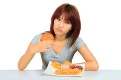 Молодая азиатская женщина с donuts на таблице Стоковое Изображение RF