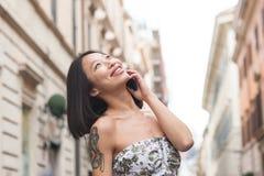 Молодая азиатская женщина усмехаясь используя сцену мобильного телефона городскую Стоковые Изображения