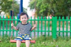 Молодая азиатская игра мальчика утюг отбрасывая на спортивной площадке под стоковое фото