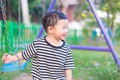 Молодая азиатская игра мальчика утюг отбрасывая на спортивной площадке под стоковые фото