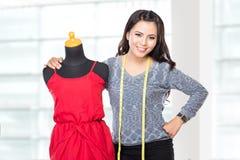 Молодая азиатская дизайнерская женщина представляя усмехаться, держит ножницы, уборную Стоковые Изображения RF