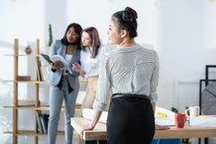 Молодая азиатская коммерсантка стоя на таблице и коллегах говоря позади Стоковое Изображение RF