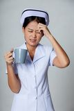 Молодая азиатская медсестра получила головную боль с чашкой кофе Стоковые Фотографии RF