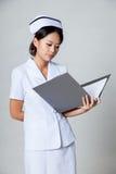 Молодая азиатская медсестра прочитала данные в связывателе кольца Стоковая Фотография RF