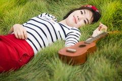 Молодая азиатская счастливая ложь женщины на зеленом поле с гавайской гитарой Стоковые Изображения