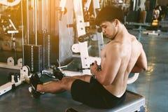 Молодая азиатская тяга спортсмена все еще утяжеляет для строя мышцы на I стоковое фото