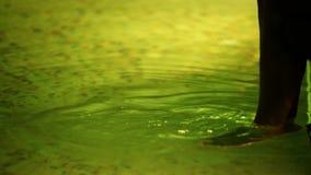 Молодая дама ласкает ноги в бассейне спа-центра акции видеоматериалы