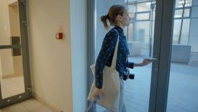 Молодая дама выходя лифт и строя к улице с чемоданом, сумкой и камерой сток-видео