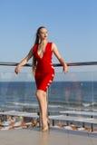 Молодая дама в красном платье представляет на балконе в роскошной гостинице Женщина с длинными волосами отдыхает на террасе ` s г стоковое изображение