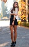 Молодая дама в платье коктеиля и высоко-накрененных ботинках представляя outdoo Стоковые Фотографии RF