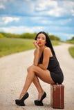 Молодая дама ждет любой автомобиль на дороге Стоковые Изображения