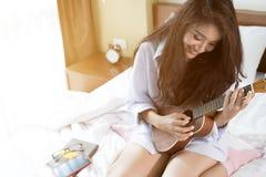 Молодая дама играя гавайскую гитару в ее спальне Стоковое Изображение