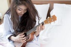Молодая дама играя гавайскую гитару в ее спальне Стоковое Фото