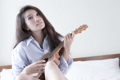 Молодая дама играя гавайскую гитару в ее спальне Стоковые Изображения RF