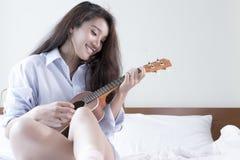 Молодая дама играя гавайскую гитару в ее спальне Стоковые Фото