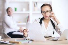 Молодая дама на телефоне делая обработку документов Стоковые Фото