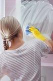 Молодая дама обтирая зеркало с голубой тканью и специальной чисткой стоковая фотография