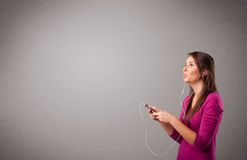Молодая дама поя и слушая к музыке с космосом экземпляра Стоковое фото RF