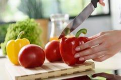 Молодая дама подготавливая овощи в кухне Стоковое Изображение