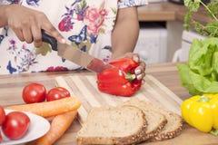 Молодая дама прерывая овощи Стоковые Изображения RF