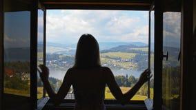 Молодая дама раскрывает окно и смотрит горы, озеро, деревню и небо видеоматериал