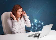 Молодая дама сидя на столе и печатая на машинке на компьтер-книжке с социальным netw Стоковые Фотографии RF