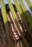 Молодая дама усмехаясь за зелеными листьями стоковые изображения