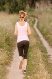 Молодая дама фитнеса бежать на сельской дороге Стоковое фото RF
