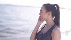 Молодая атлетическая девушка говоря телефоном на пляже акции видеоматериалы