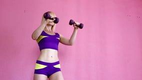 Молодая атлетическая девушка делая тренировки с гантелями в спортклубе на розовой предпосылке видеоматериал