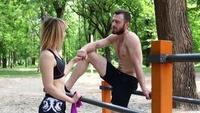 Молодая атлетическая девушка и бородатый человек говоря пока ослабляющ на тренировке в парке