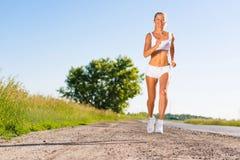 Молодая атлетическая женщина бежать на дороге стоковые фото