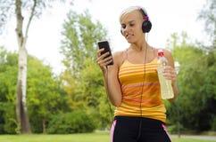 Молодая атлетическая женщина с умным телефоном Стоковая Фотография