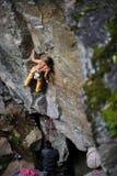 Молодая атлетическая мужская стена скалы альпиниста утеса взбираясь Скопируйте космос на праве Стоковые Фото